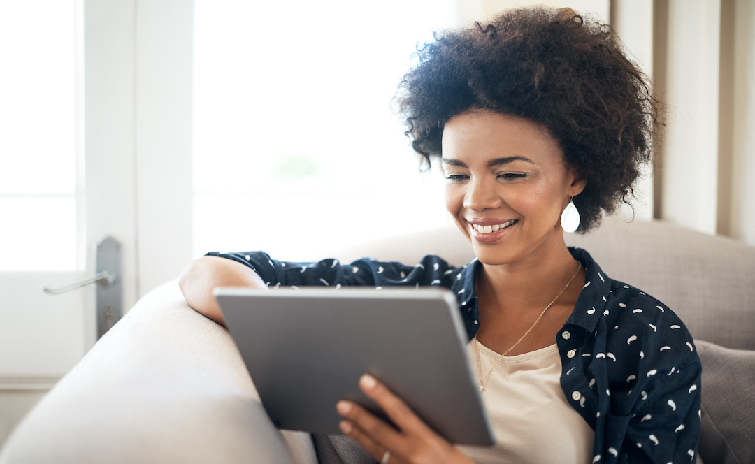 Young woman relaxing at home with her digital tablet